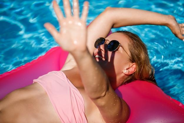 プールのマットレスで休んで日光浴をしているサングラスの女性モデル。膨脹可能なピンクのマットレスに浮かぶピンクのビキニ水着の女性。 spfと日焼け止め