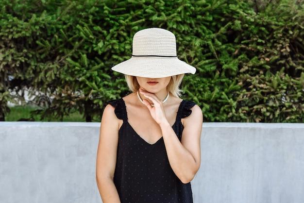 거리 옷 카탈로그에 태양 모자에서 포즈를 취하는 여성 모델