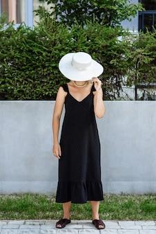옷과 태양 모자 카탈로그의 새로운 컬렉션에서 포즈를 취하는 여성 모델