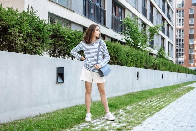 가옥을 배경으로 도시 야외에서 새로운 옷을 입고 포즈를 취한 여성 모델