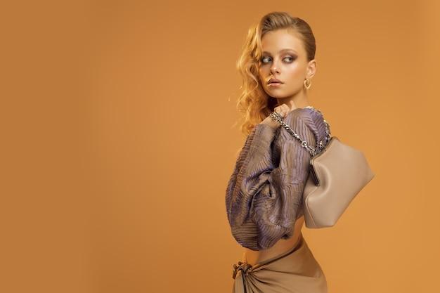 Модель женщины позирует в студии, женщина в стильной модной одежде, юбка и блузка с широкими рукавами. фото высокого качества