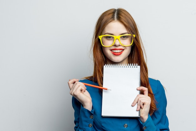 Woman model posing with glasses on a, emotions with a notebook in her hands, mock up