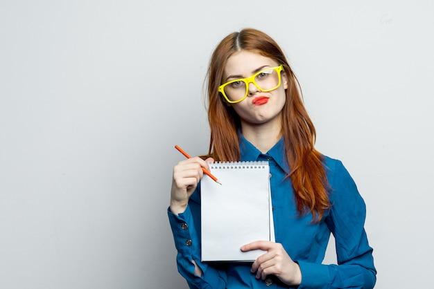 Женщина модель позирует в очках на светлом пространстве, эмоции с ноутбуком в руках, макет
