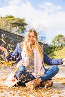 Woman model sitting on windy autumn ground