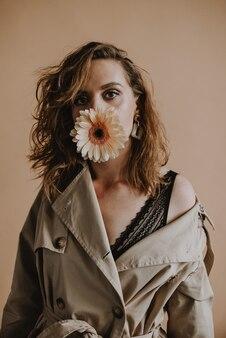 여성 모델은 어깨를 낮추고 입에 거베라 꽃을 물고 베이지색 트렌치 코트를 입고 서 있습니다. 프리미엄 사진