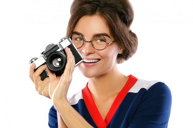 Woman model in vintage look holding retro camera in her hands