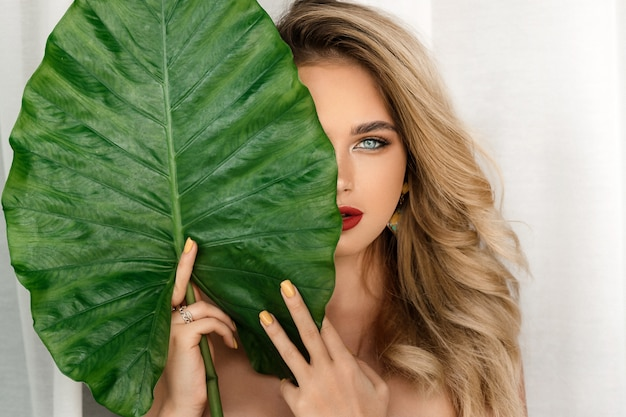 Woman model with bright makeup and healthy skin with green leaf plant