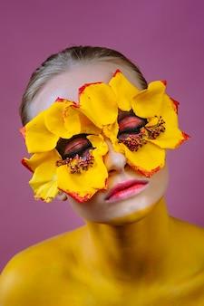 Модель женщины с желтыми цветами вокруг глаз. тело женщины окрашено в желтый цвет