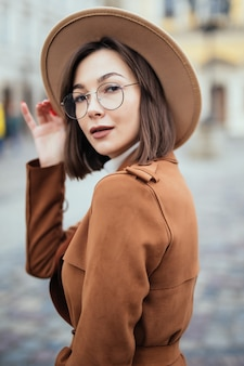 Woman in modern glasses and fashion hat and brown coat is posing in city cenre