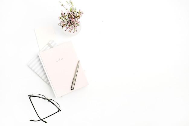 白い背景にノート、メガネ、ペン、野生の花の花束を持つ女性のモダンな最小限のホーム オフィス デスク。フラットレイ、トップビュー