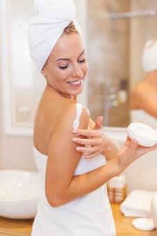 シャワーの後、女性が腕に潤いを与える