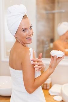 여성은 샤워 후 몸에 수분을 공급합니다.