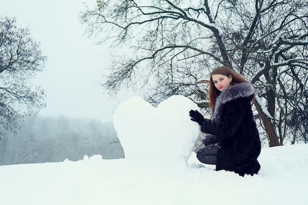 Женщина лепит из снега большое сердце