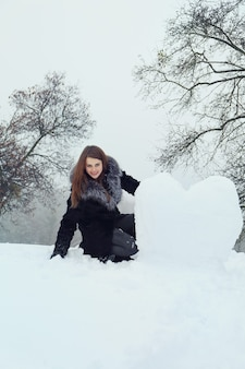 Woman molds a big heart out of the snow
