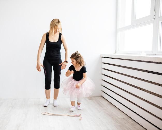 女性のお母さんは彼女の小さな娘と一緒に踊りにふける、白いインテリアで体操に従事しています