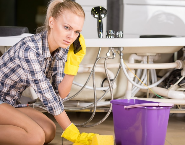 Woman mopping up and calling to plumbing.