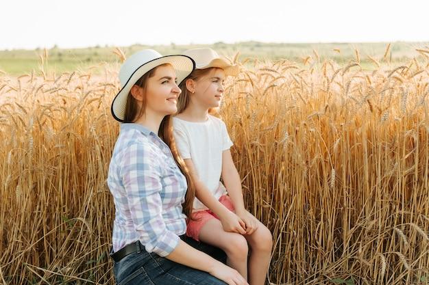 Женщина, мать и дитя, ее дочь в сельской местности возле пшеничного поля семья фермеров вид сбоку мо ...