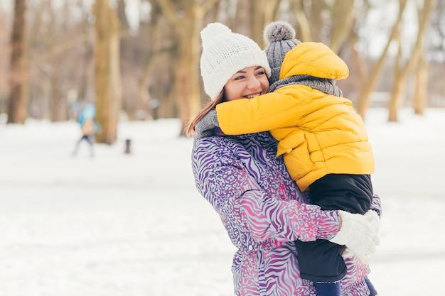 Женщина-мать гуляет и отдыхает со своими маленькими сыновьями, в зимнем парке, весело