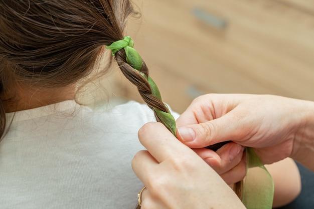 Женщина, мама плетет косы на волосах девушки цветными лентами