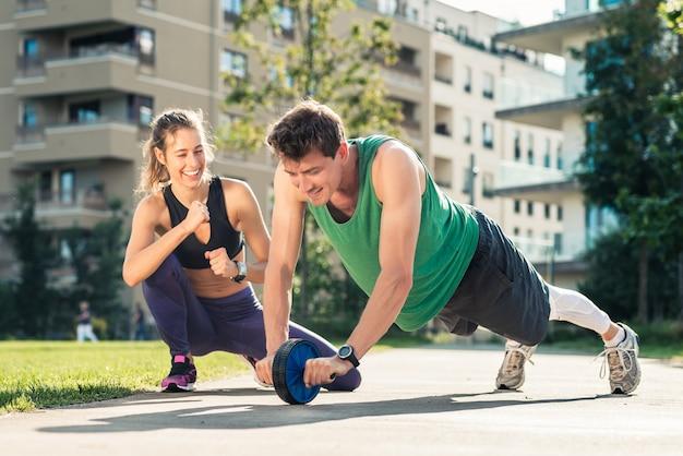 Woman motivating man exercising with toning wheel