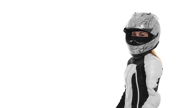 Портрет женщины мотоциклист на белом фоне. девушка в мотоциклетном шлеме в кожаном костюме мотоцикла. свободное место.