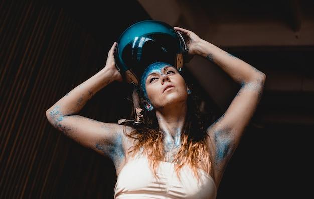 Женщина-мотоциклист надел защитный шлем. портрет красивой женщины с голубыми блестками на лице