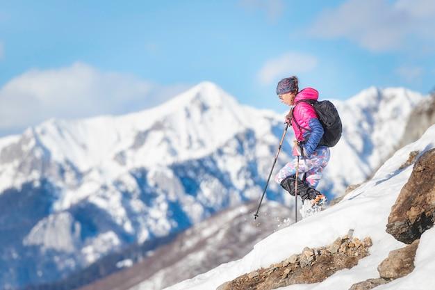 Женщина-альпинист спускается с кошек на снежном склоне
