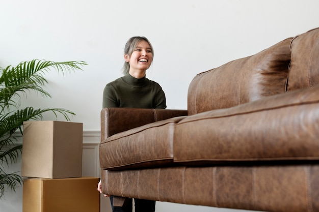 Женщина перемещает диван в новом доме