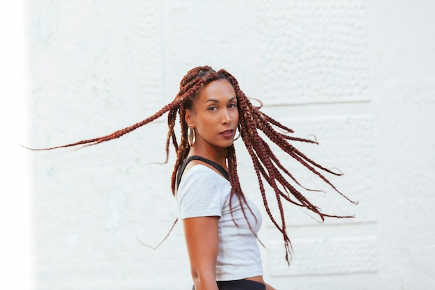 Woman moving her long braids isolated a white wall