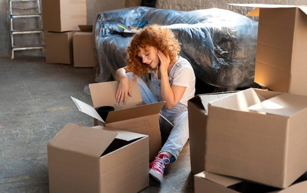新しい家に引っ越して、持ち物で段ボール箱を分類する女性