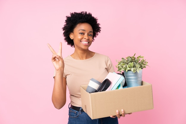 Woman moving to a new house over pink wall