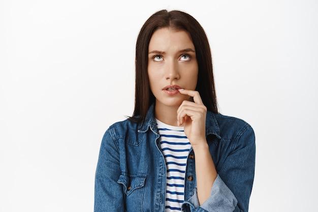 心の中でマルチプレイする女性、思慮深く噛む指を見上げ、smthを熟考し、決定を下し、頭の中でパズルを解き、白の上に立つ