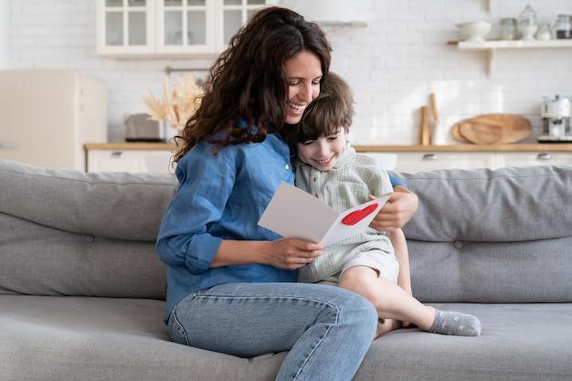 女性のミイラは子供から贈り物を得る幸せなママは母の日に小さな息子からグリーティングカードを読んで楽しんでいます