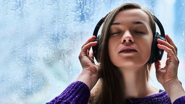 무선 헤드폰에 닫힌 눈을 가진 여자 음악 애호가가 즐기는 비오는 가을 날씨 동안 진정 진정 편안한 음악을 듣고