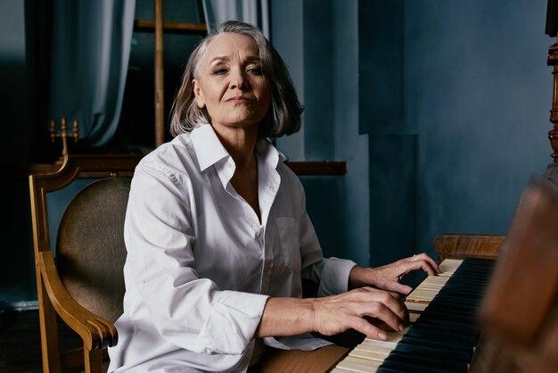 Учитель музыки женщина сидит возле пианино