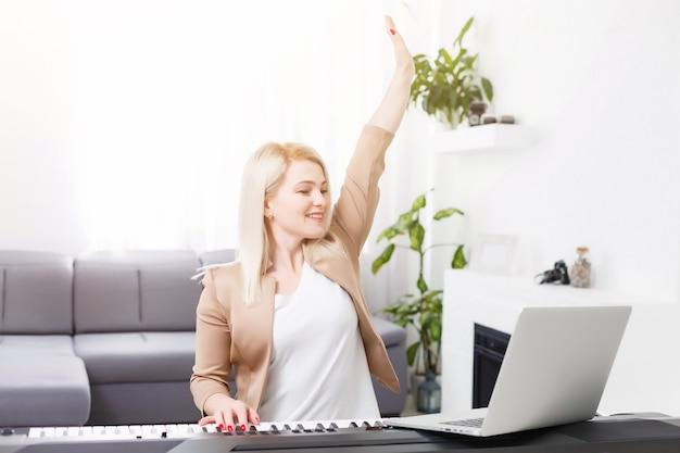집에서 온라인 수업을 하는 동안 집에서 클래식 디지털 피아노를 연주하는 여성 음악가, 격리 중 사회적 거리, 자가 격리, 온라인 교육 개념