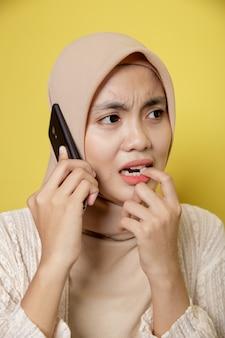 노란색 배경에 고립 된 호출 전화 슬픈 표정으로 hijab를 입고 여자 이슬람