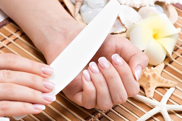 Donna in un salone di bellezza che riceve manicure da un'estetista. concetto di trattamento di bellezza.
