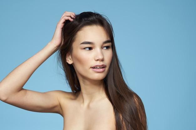女性の裸の肩のヘアケアのクローズアップ銀行と青い背景