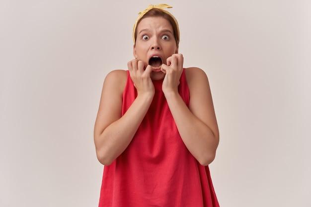 Donna trucco naturale emozione ha sottolineato terribile spaventoso terribile spaventoso terribile panico con i pugni sul viso indossando camicetta rossa alla moda e bandana bianca