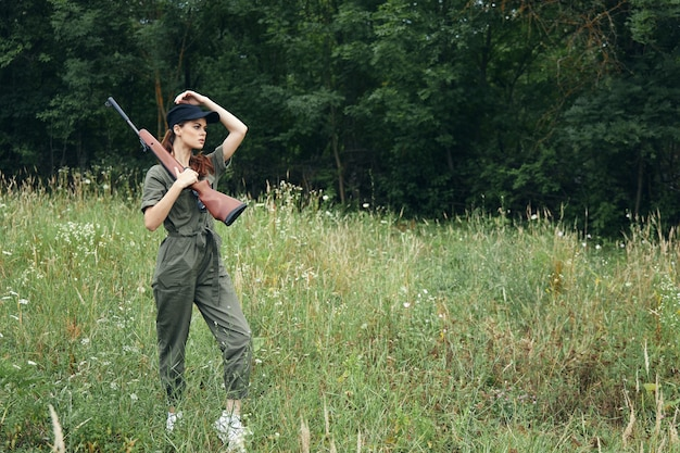 Woman on nature arms on shoulder travel hunting lifestyle black cap green trees on background