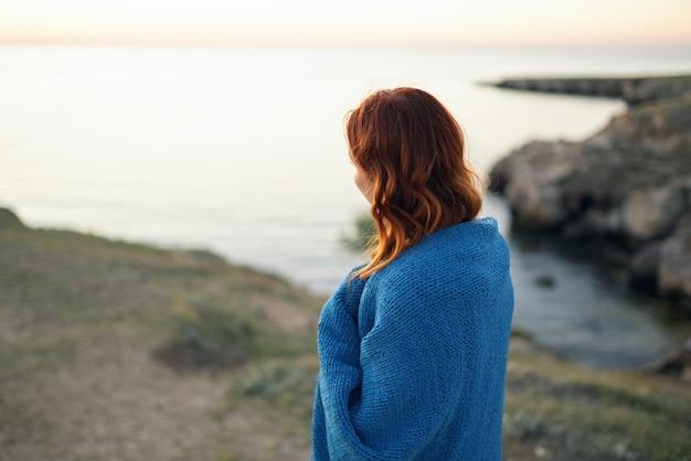 Woman on nature blue plaid admires the landscape travel