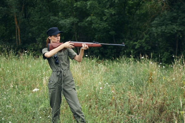 Woman on nature green overalls with a gun in front of him fresh air green trees on background