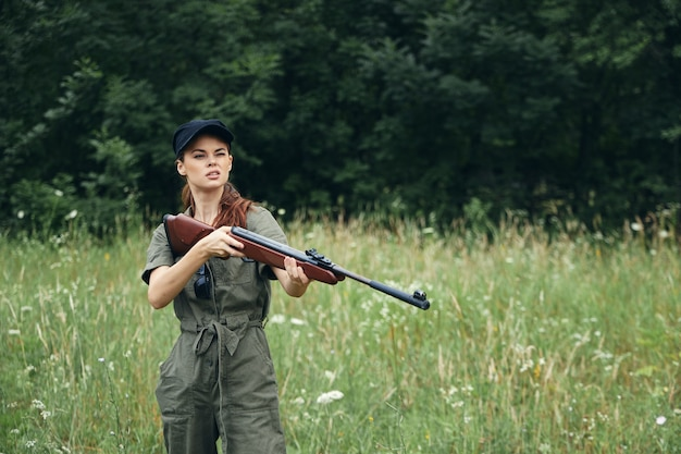 Woman on nature gun in hand fresh air traveler hunting green overalls