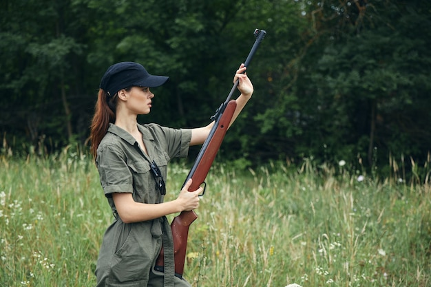Woman on nature with a gun in his hands black cap green jumpsuit shooting fresh air cropped view