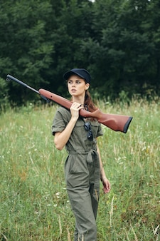Woman on nature with a gun in his hands looking to the side green overalls fresh air forest background