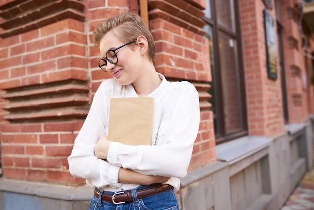 通りの教育機関で彼女の手に本を持った眼鏡のレンガ造りの建物の近くの女性