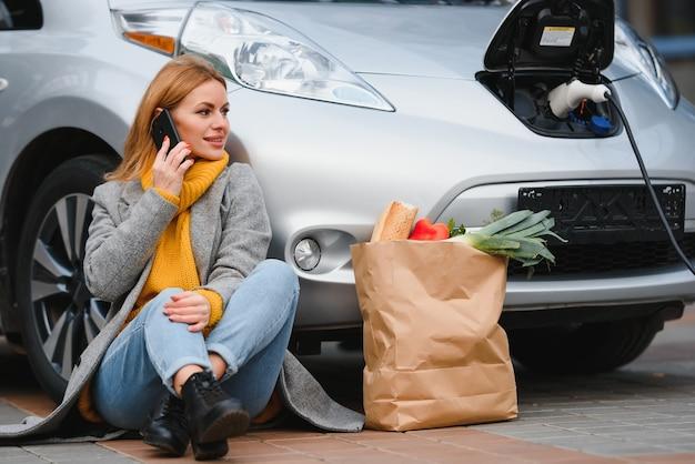 Женщина возле прокатного электромобиля. автомобиль заряжен на зарядной станции.