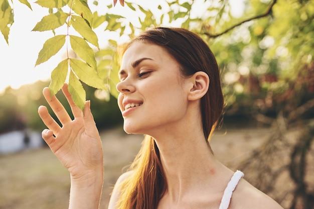 풀밭에서 자연에 잎을 가진 나무 근처 여자