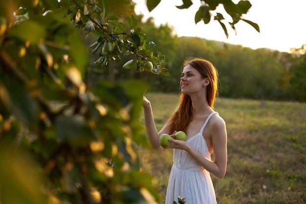 自然の中で白いドレスを着たリンゴの木の近くの女性